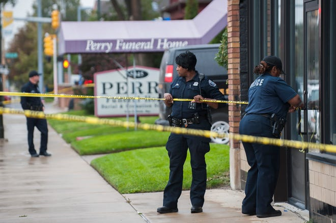 Detroit police officers use crime scene tape to cordon off an area while they execute a search warrant at Perry Funeral Home in Detroit on Oct. 19.
