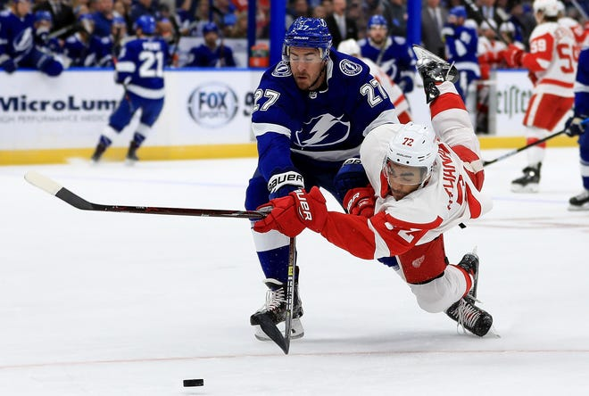 Red Wings' Andreas Athanasiou, right,  and Lightning's Ryan McDonagh fight for the puck during Thursday's game.