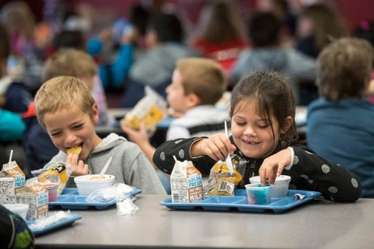 Konner Jameson, left, laughs after telling a joke to Brylei Sams while the first graders enjoy lunch together at Hebron Elementary school on Friday, Oct. 19, 2018.