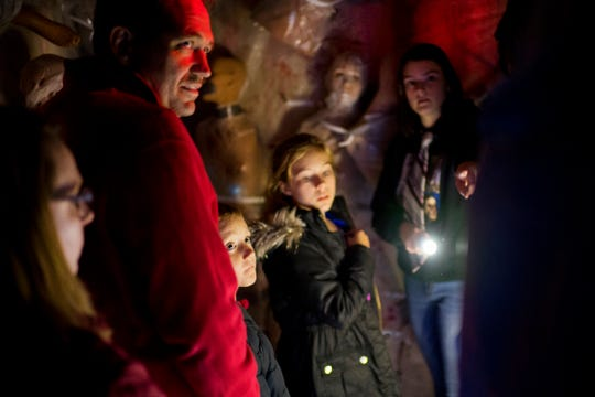 A no-scare tour of the Newburgh Civitan Zombie Farm offers youngsters, Owen Meier, 8, bottom left, and Izzy Mackiewicz, 11, center, a chance to see the tricks employed to scare visitors under the light of the tour guides' flashlights Thursday evening.