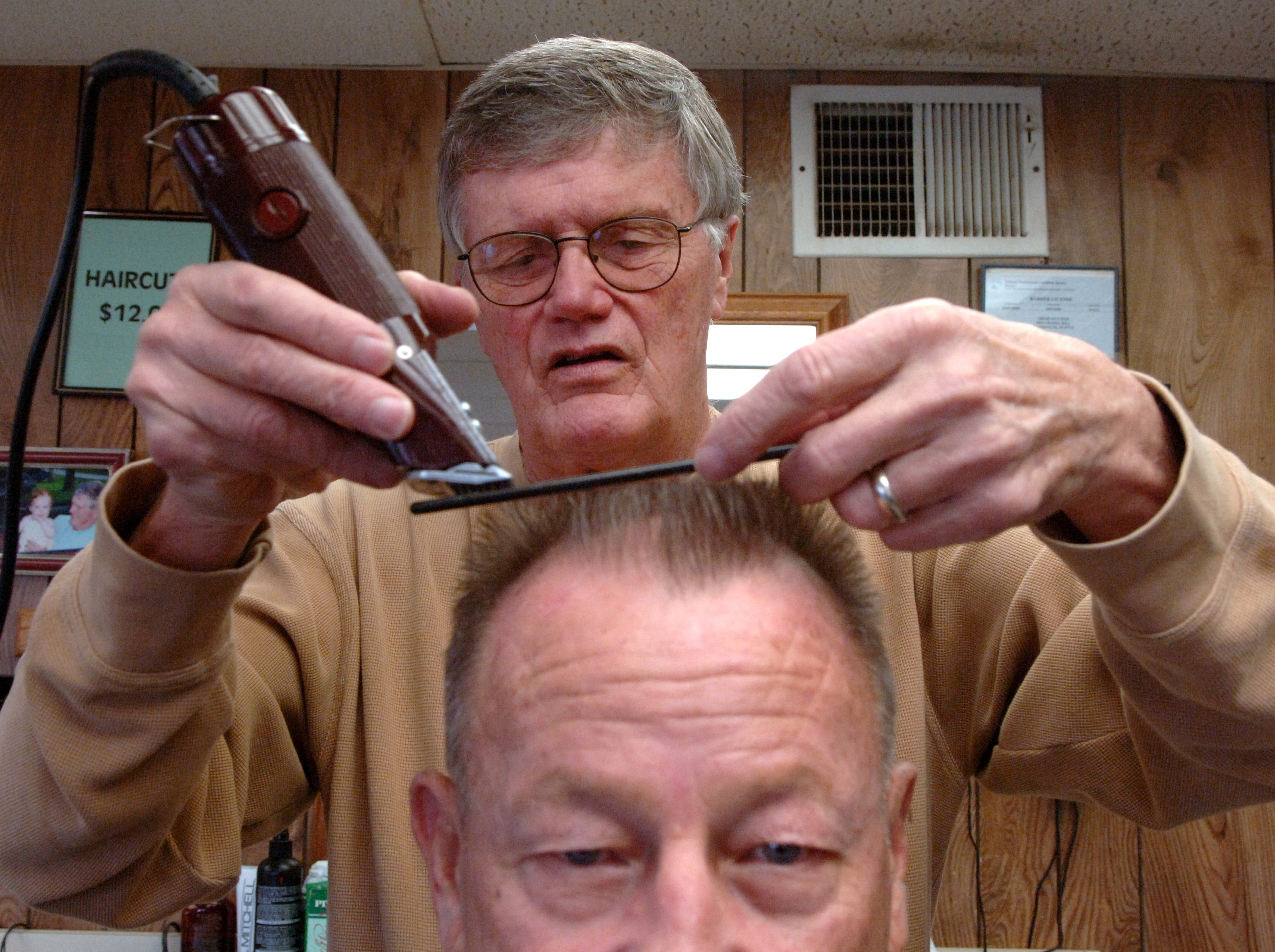 Eddie Geis, shown here in a 2007 photograph, died on Thursday at age 77. In this photo, he was cutting Bud Gatewood's hair. Geis had been Gatewood's barber since Geis was an apprentice in 1961.