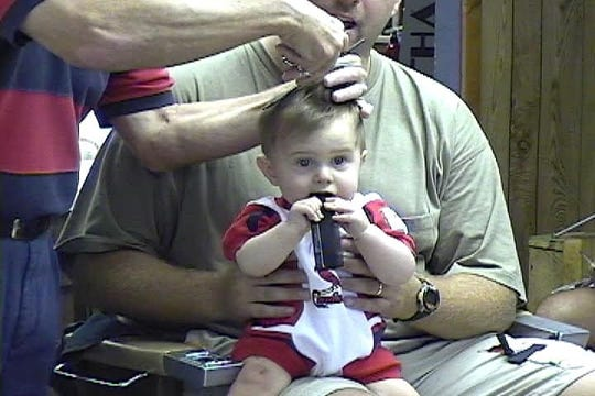 It was a tradition for Eddie Geis' customers to take their sons (and sometimes daughters) to Eddie for a first haircut. Here, Shawn Fetscher (who's now a senior at Reitz High School) gets a trim from Eddie.