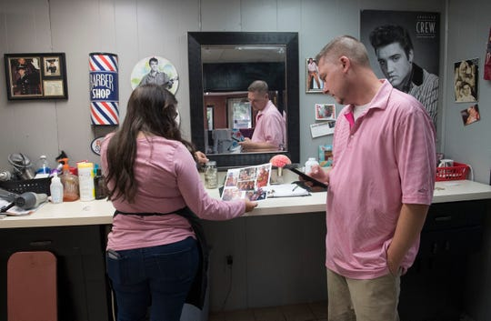 Lisa Morris and Mike Seibert look over old photos while mourning the lost of their boss Eddie Geis Friday afternoon at Eddie Geis's Barber & Beauty Shop. Geis passed away Thursday at age 77 after a battle with cancer and was widely respected on the Westside of Evansville.