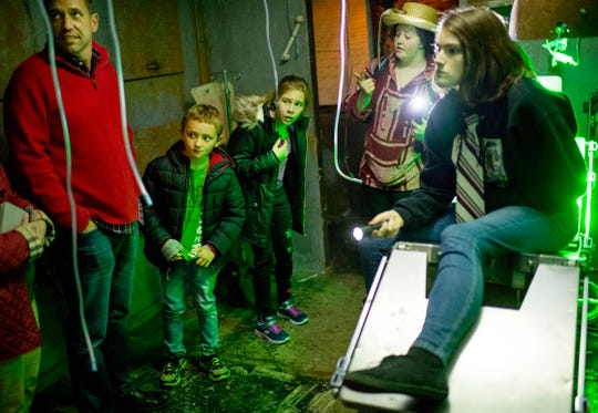 Youngsters Owen Meier, 8, second left, and Izzy Mackiewicz, 11, center, get a look into the haunted workings of the operating room at the Newburgh Civitan Zombie Farm during a no-scare tour Thursday evening.