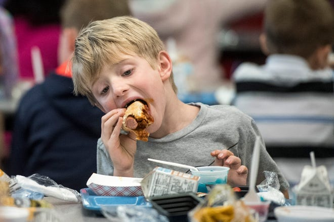 First grader Stephen Martin chomps down on a chili dog while eating lunch at Hebron Elementary school on Friday, Oct. 19, 2018.