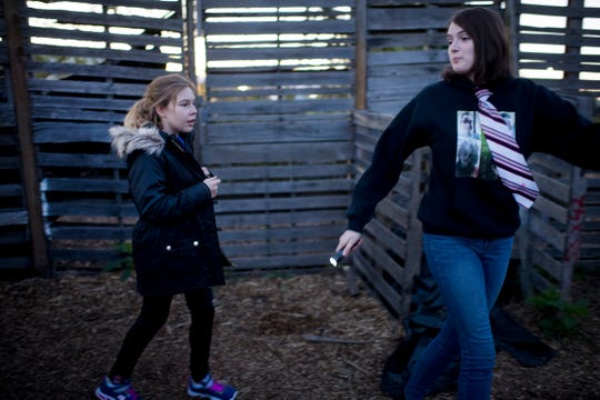 Tour guide Mary Reed, 17, leads Izzy Mackiewicz, 11, through an outdoor maze during a no-scare tour at the Newburgh Civitan Zombie Farm Thursday evening.