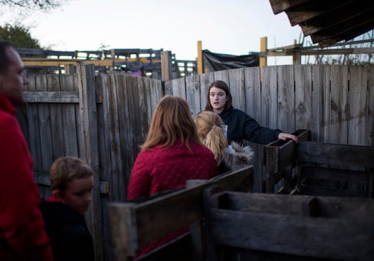 Tour guide Mary Reed, 17, center, leads her charges on a tour of the Newburgh Civitan Zombie Farm during a no-scare tour Thursday evening.