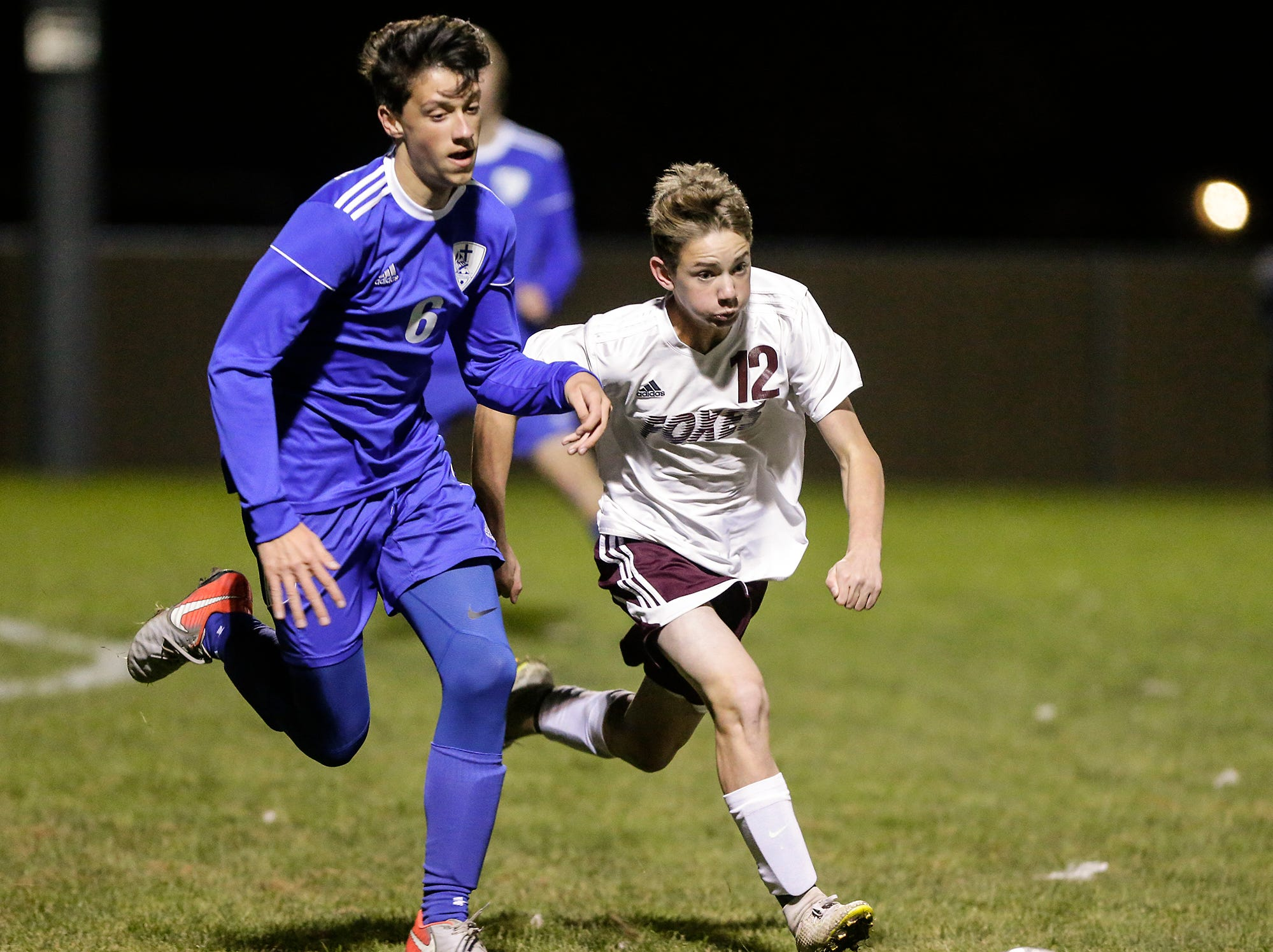 Winnebago Lutheran Academy soccer's Colin Knoblock and Omro High School's Kaden Besaw race for the ball during their WIAA regional playoff game Thursday, October 18, 2018 in Fond du Lac, Wisconsin. Doug Raflik/USA TODAY NETWORK-Wisconsin