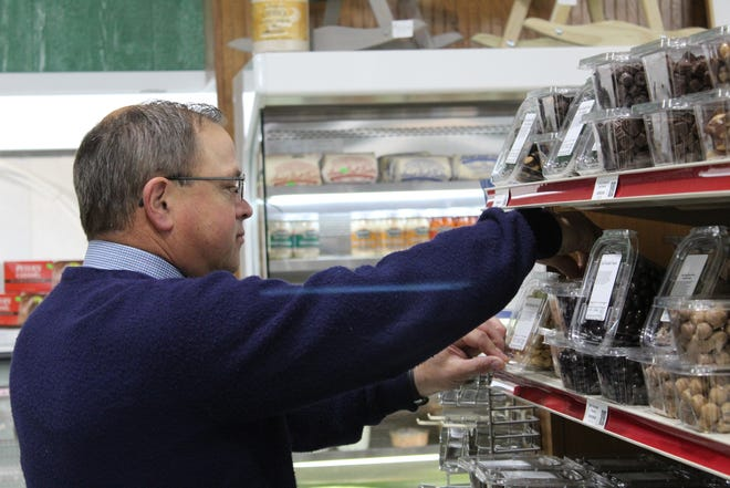 Bark Creek Pantry owner Steven Horst adjusts bulk food items that include candies, chocolates and other snacks unique to Fremont.