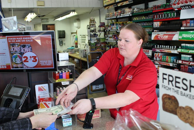 Rachel Reese, a cashier at Circle K, 1022 E. State St., hands a customer a Mega Millions lottery ticket Friday. The jackpot hit $1 billion Friday afternoon.