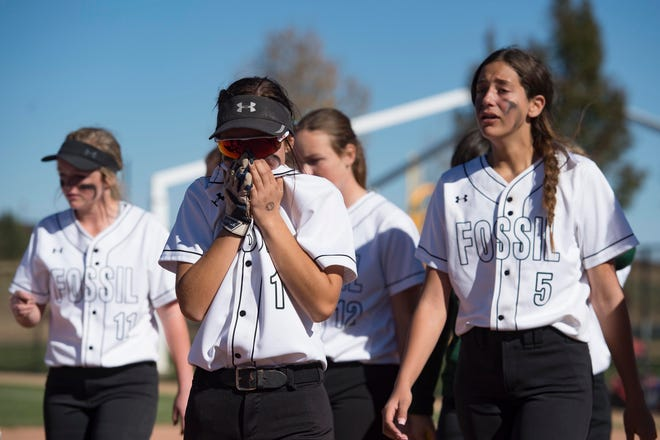 Fossil Ridge High School softball players react after the team's 3-2 nine-inning loss to Regis in the first round of Class 5A state softball tournament Friday at the Aurora Sports Park in Aurora.
