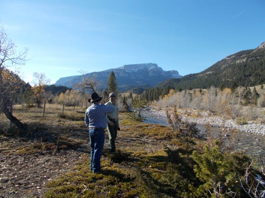 """With Steamboat Mountain in the background, Dan Barrett discusses his land with Mike Munoz, district ranger of the U.S. Forest Service's Rocky Mountain Ranger District, on Friday a long the Dearborn River.  Barrett plans to sell 422 acres to the Rocky Mountain Elk Foundation which in turn plans to convey it to the Forest Service. The sale will provide public access to an additional 26,000 acres on Helena-Lewis and Clark National Forest. """"That's quite the trade off, 422 acres for 26,000,"""" Munoz said."""