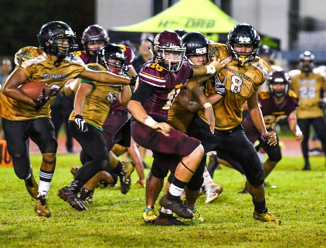 In this file photo from Oct. 19, John F. Kennedy High School Islanders' Deante Delgado (13) edges by Father Duenas Memorial School Friars defenders during their IIAAG High School Football playoff game at the GW field. Delgado and a host of high school's best strap it on one more time in the PDN's Game of the Week.