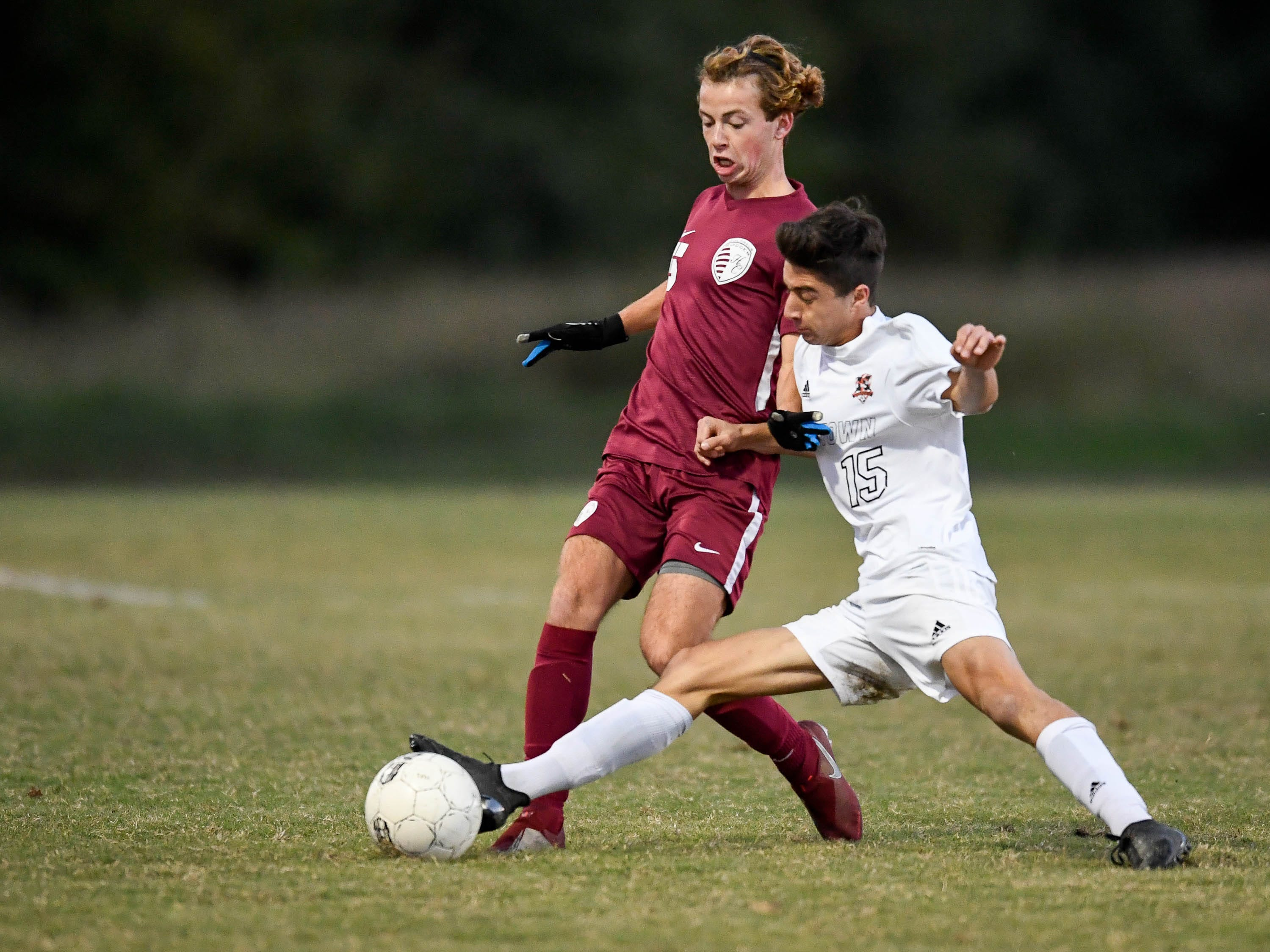 Henderson County's Cale Wright (5) and Hopkinsville's Tyler Greenwell (15) battle for the ball as the Henderson County Colonels play the Hopkinsville Tigers in the regional final at Madisonville-North Hopkins High School Thursday, October 18, 2018.