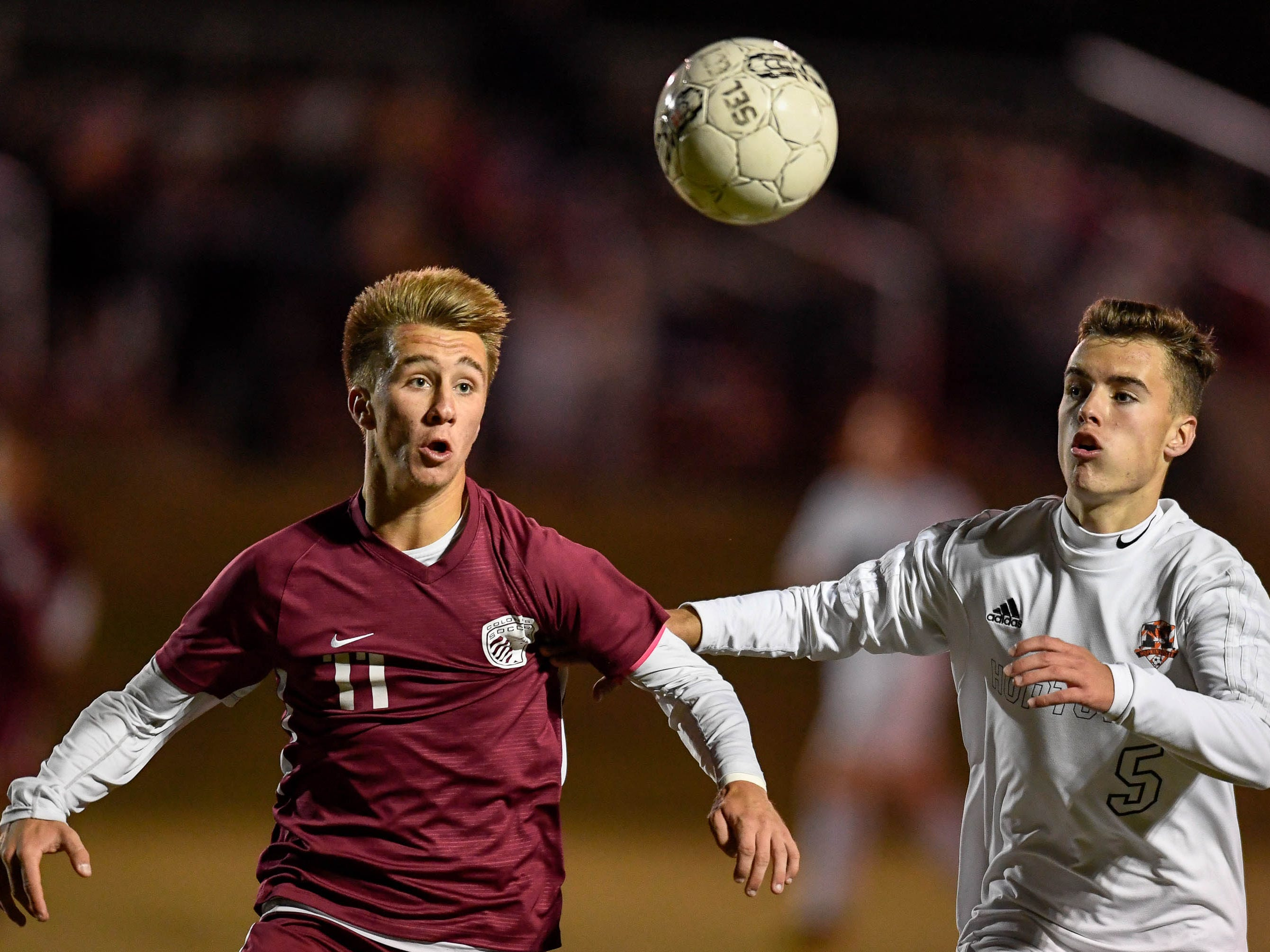 Henderson County's Max Wawrin (11) and Hopkinsville's Mason Rye (5) go for the ball as the Henderson County Colonels play the Hopkinsville Tigers in the regional final at Madisonville-North Hopkins High School Thursday, October 18, 2018.
