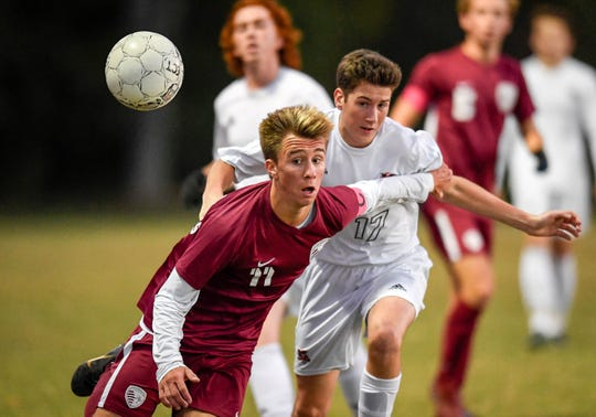Henderson County's Max Wawrin (11) and Hopkinsville's Trace Pound (17) battle for control of the ball as the Henderson County Colonels play the Hopkinsville Tigers in the regional final at Madisonville-North Hopkins High School Thursday, October 18, 2018.