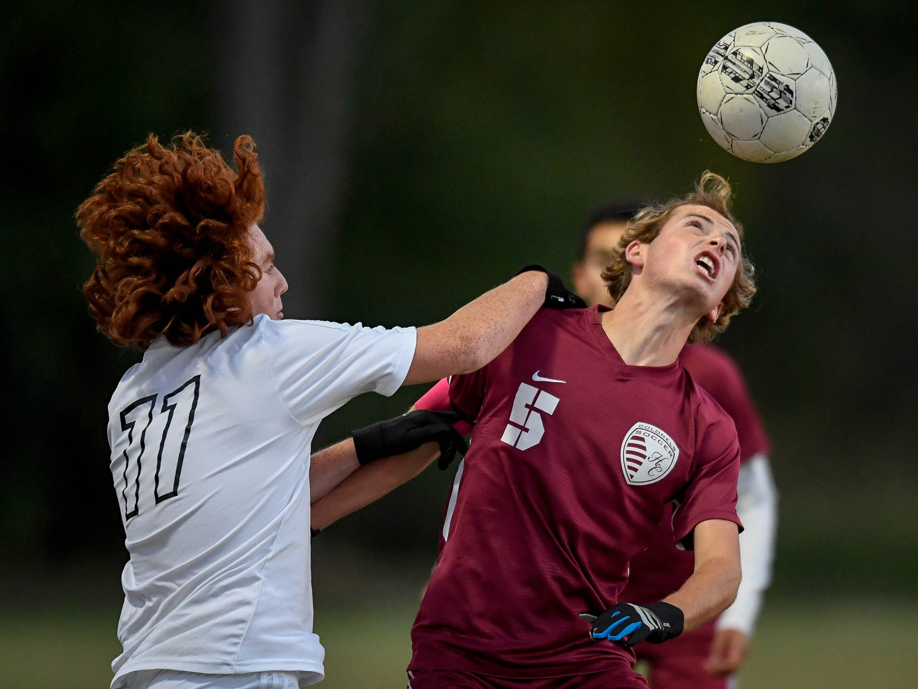 Henderson County's Cale Wright (5) heads the ball under defensive pressure from Hopkinsville's Welby Horn (11) as the Henderson County Colonels play the Hopkinsville Tigers in the regional final at Madisonville-North Hopkins High School Thursday, October 18, 2018.