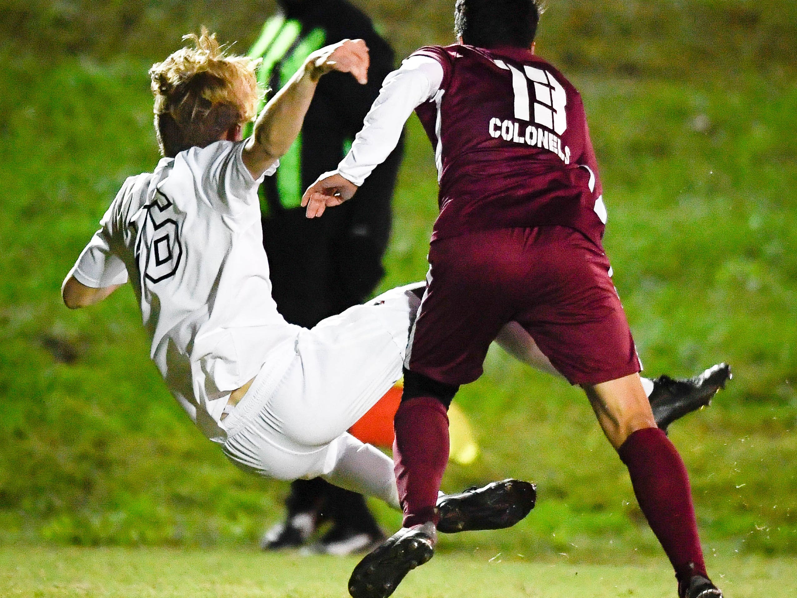 Hopkinsville's Zach Moore (16) and Henderson County's Ed Zeron (13) get tangled up as the Henderson County Colonels play the Hopkinsville Tigers in the regional final at Madisonville-North Hopkins High School Thursday, October 18, 2018.