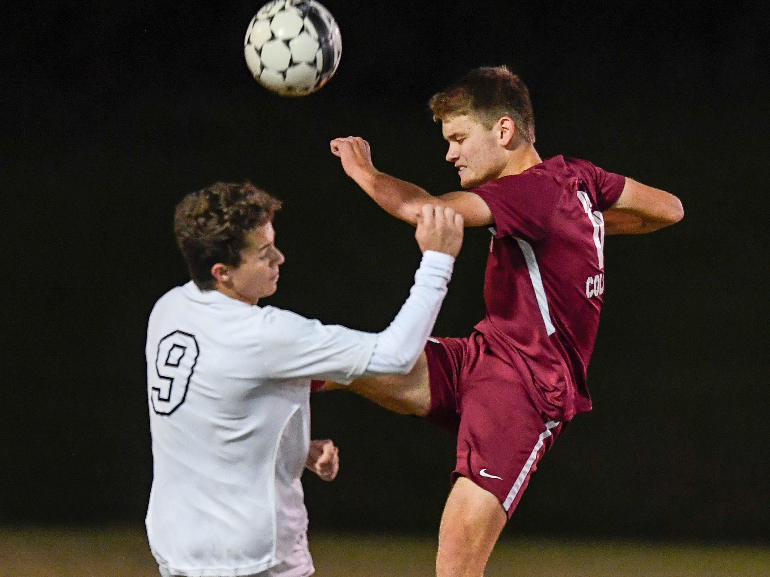 Hopkinsville's Ryan Roussel (9) and Henderson County's Lucas Butler (16) battle for control of the ball as the Henderson County Colonels play the Hopkinsville Tigers in the regional final at Madisonville-North Hopkins High School Thursday, October 18, 2018.