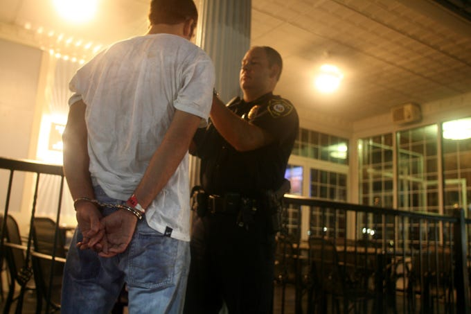 """Iowa City Police Officer Darin Zacharias issues a breathalizer test to an 18-year-old outside """"The Summit,"""" Thursday August 23, 2007, in downtown Iowa City, Iowa."""