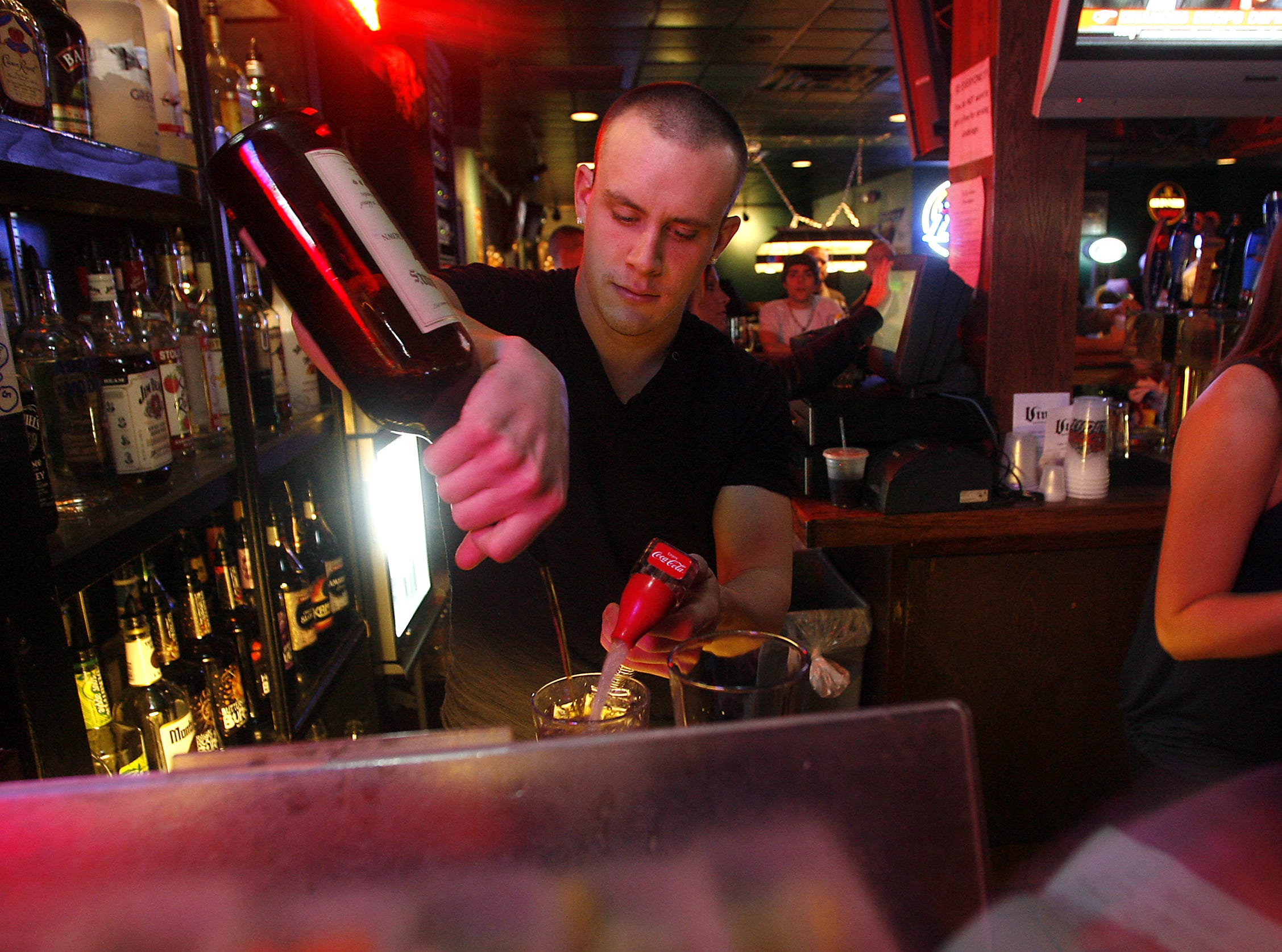 Danny Lake mixes drinks for happy hour customers while tending bar at The Vine, Friday, Dec. 4, 2009, in Iowa City, Iowa.