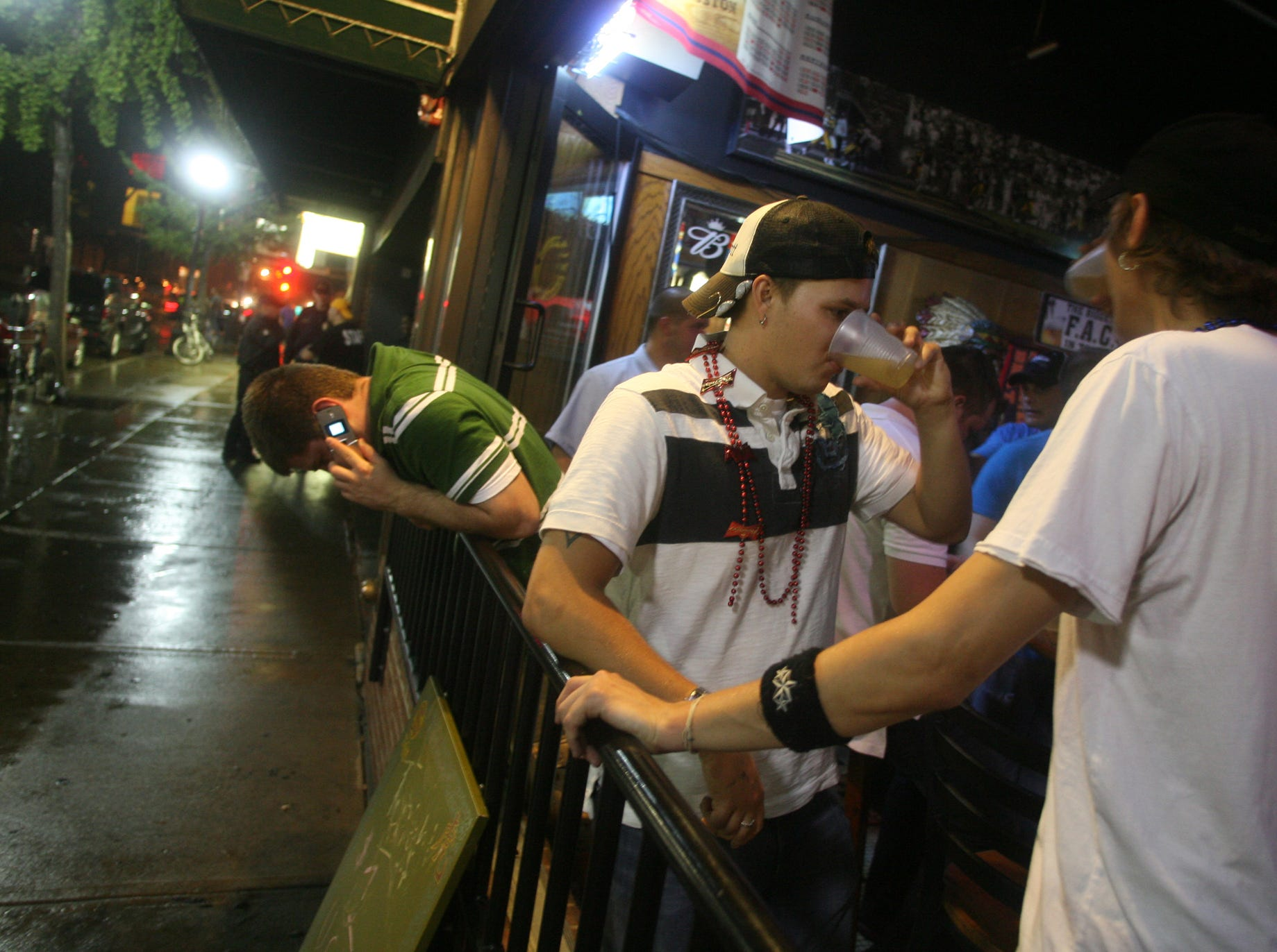 Ryan Kramer,center, and Drew McKnight, right, drink beer at the Sports Column, on Thursday, Aug. 23, 2007, in downtown Iowa City, Iowa.