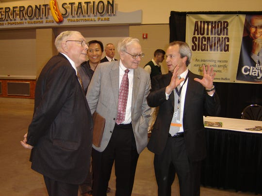 Left to right, Charlie Munger, vice chairman of Berkshire Hathaway, and Chairman and CEO Warren Buffett speak with Clayton Homes CEO Kevin Clayton at Berkshire's 2005 annual meeting in Omaha.