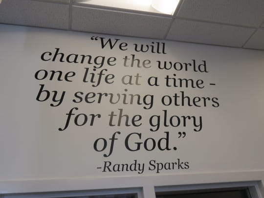 Saying on wall of Sparks Insurance office displays firm's theme of Christian service.