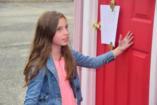 Marley Phillips checks the door to determine if it's hot or cold during a fire safety demonstration held at Karns Elementary School Tuesday, Oct. 16.
