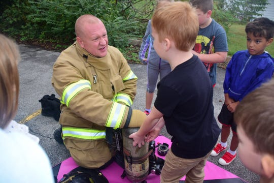 Firefighter Greg Parton explains his oxygen mask and tank to Wyatt Moulton, 6, and his first grade classmates during a fire safety demonstration held at Karns Elementary School Tuesday, Oct. 16.