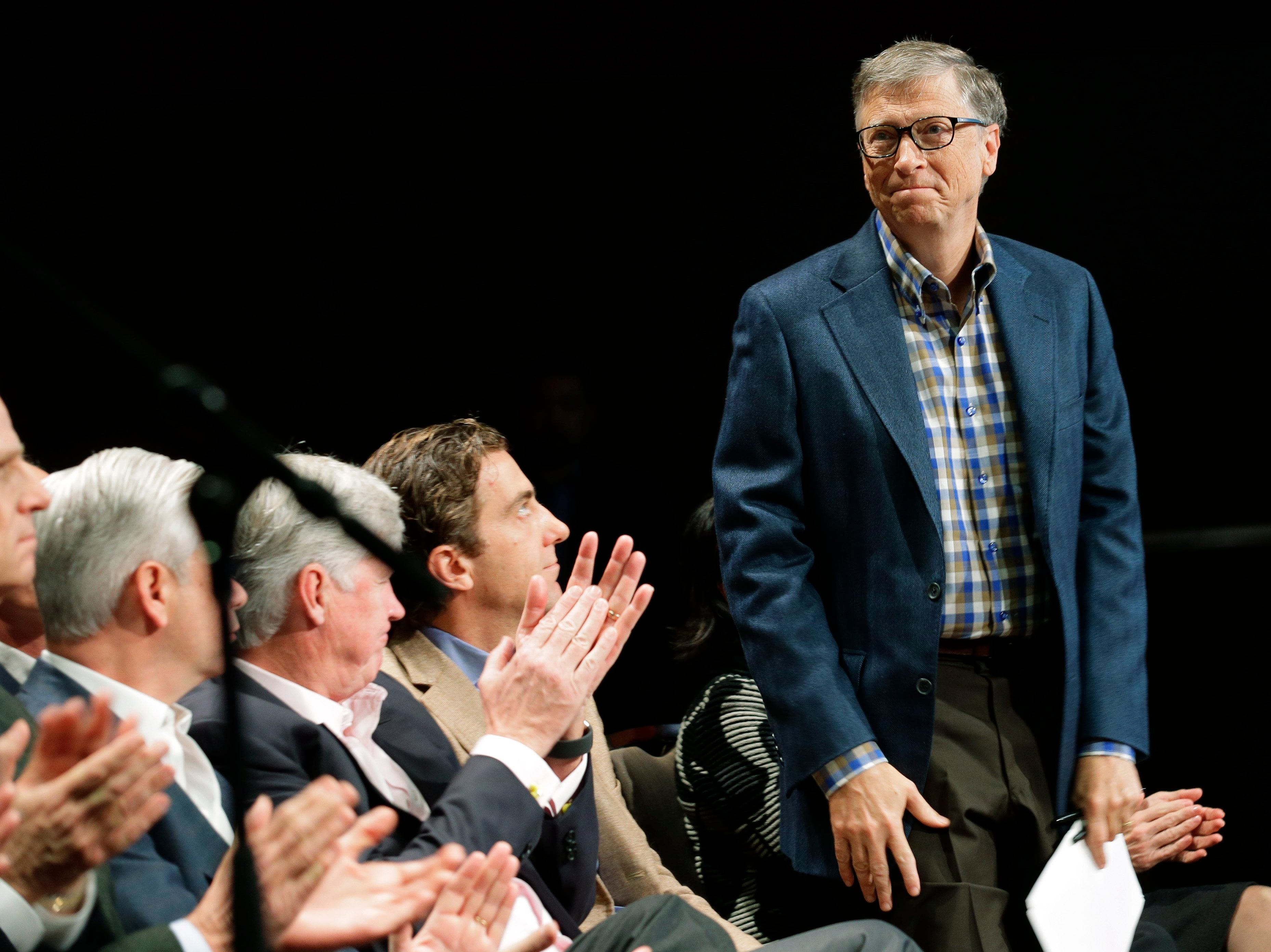 Microsoft Corp. founder Bill Gaes, right, is introduced Wednesday, Dec. 2, 2015, as he attends Microsoft's annual shareholders meeting in Bellevue, Wash.
