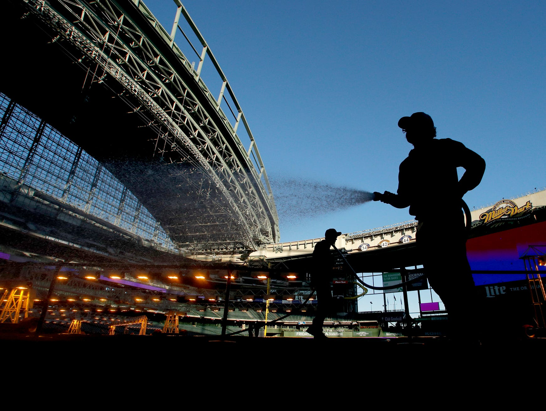 A member of the Miller Park grounds crew waters the turf on an off day in the National League Championship Series Thursday, Oct. 18, 2018, in Milwaukee. The Las Angeles Dodgers and the Milwaukee Brewers are scheduled to play Game 6 of the baseball series on Friday. (AP Photo/Charlie Riedel)