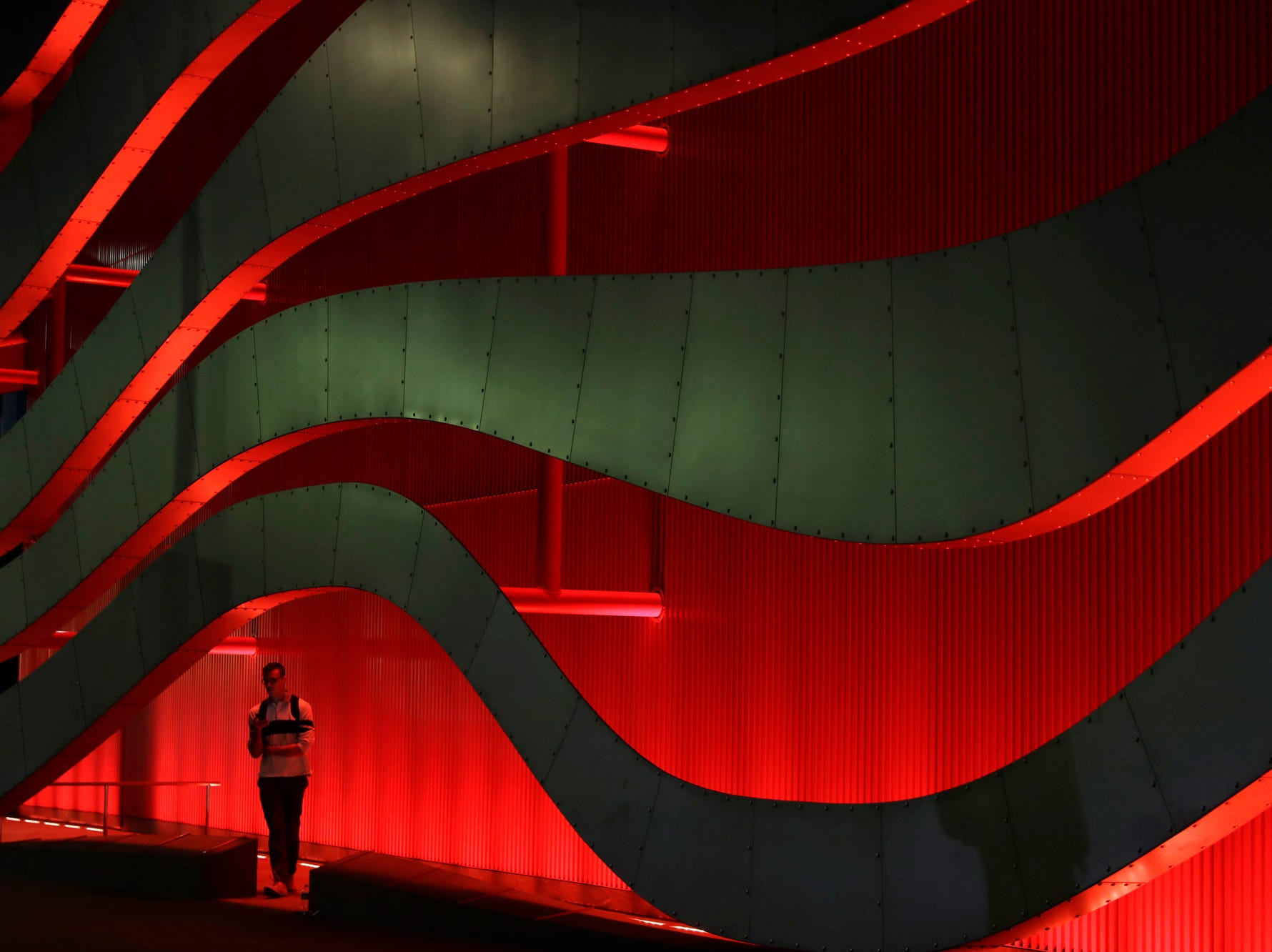 A man pauses to check his cell phone under the colorful architecture outside of the Petersen Automotive Museum Thursday, Oct. 18, 2018, in Los Angeles. (AP Photo/Marcio Jose Sanchez)
