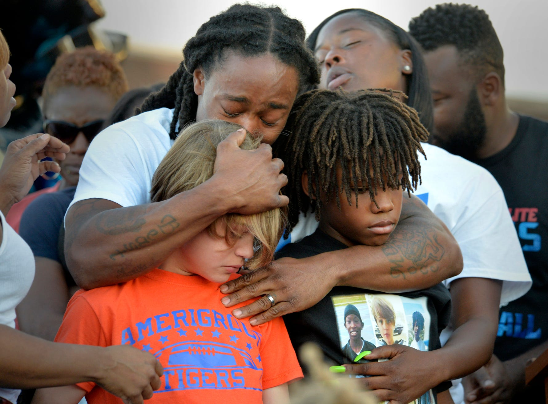 Melquan Robinson, Sr., and Chinikka Jackson, parents of electrocution victim Melquan Kwame Robinson, 12, embrace, from left, David Sette, 11, and Traqwon Berry, 13, who were both injured trying to pull their friend to safety when he was electrocuted while touching a fence that was in contact with a live wire at a ball field during a vigil at the Bernie Ward Community Center in Augusta, Ga., Thursday, Oct. 18, 2018, (Michael Holahan/The Augusta Chronicle via AP)