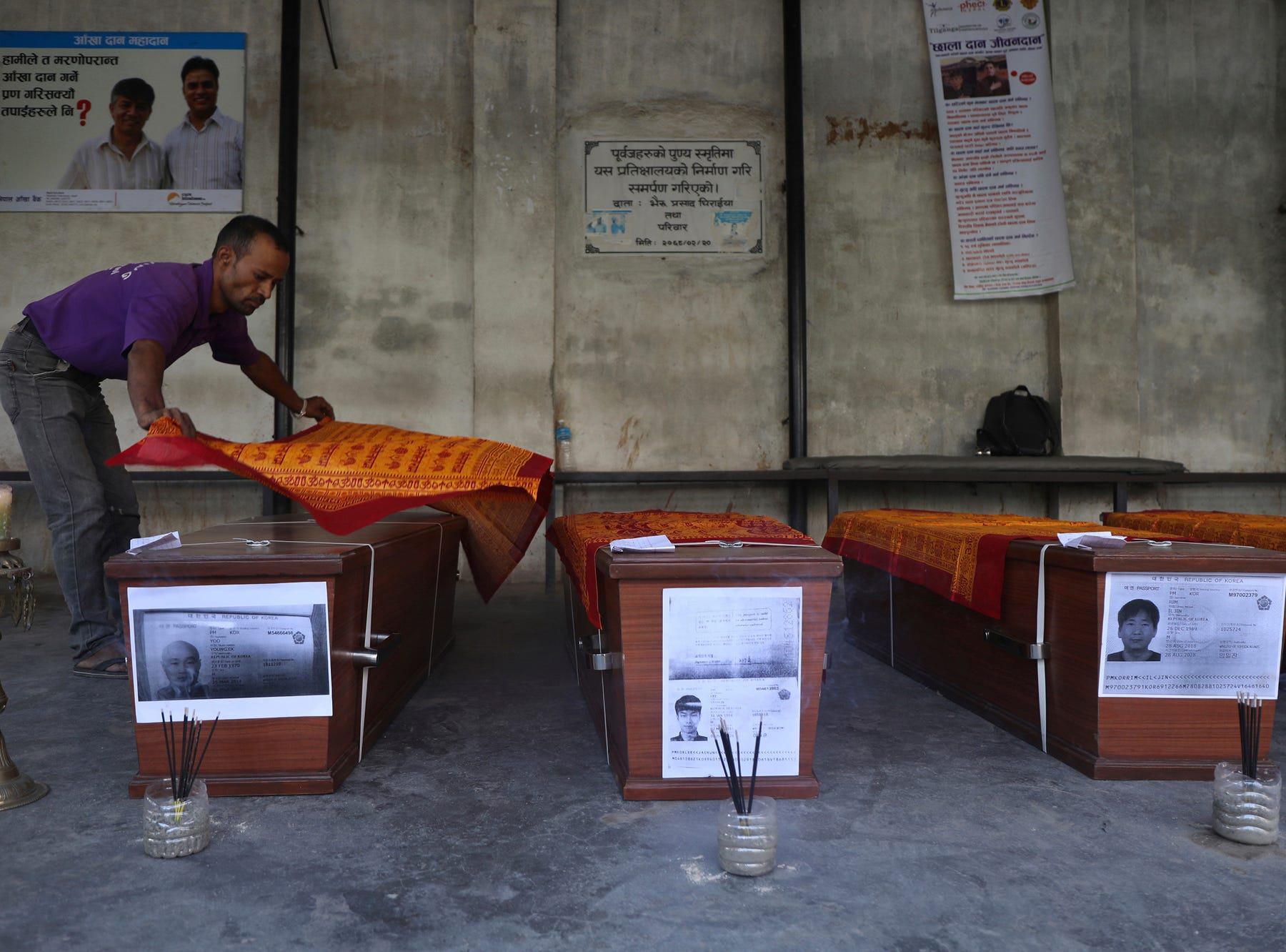 A man offers sacred scarves on coffins containing bodies of South Korean climbers killed over the weekend in a fierce storm on Nepal's Gurja Himal mountain after theywere brought to the Tribhuvan University Teaching Hospital in Kathmandu, Nepal, Tuesday, Oct. 16, 2018. The bodies were driven to the airport and were set to be flown to Seoul, South Korea's capital, later Tuesday. The bodies of five South Korean climbers are heading home amid calls to improve weather warning systems on Nepal's mountains. (AP Photo/Bikram Rai)