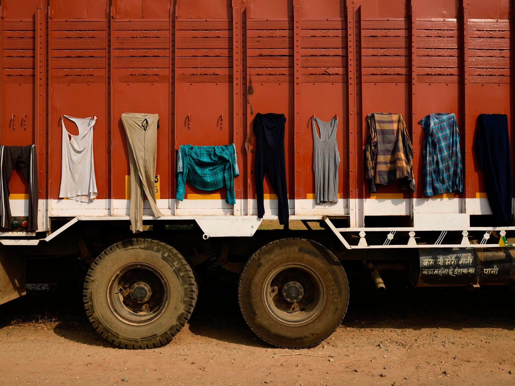 Clothes belonging to truck drivers are hung out to dry on the body of a truck in Mathura, India, Friday, Oct. 19, 2018. Truck drivers and their assistants spend weeks on the road making the highway their home. (AP Photo/R.S. Iyer)
