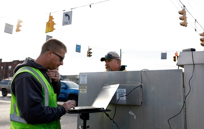 Lancaster Department of Transportation employees Charlie Mullett, left, and Doug Bennett work install a new legacy processor to connect a traffic control camera to the a new fiber optic network that some Lancaster traffic light operate on. The network allows LDOT employees to monitor traffic at the connected intersections and from the department's main office.