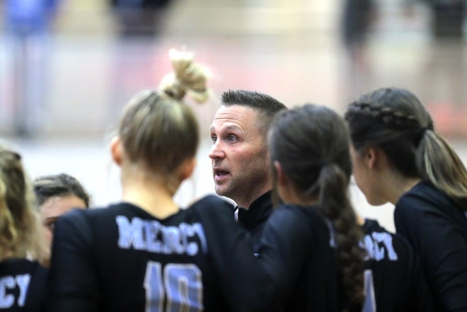 Mercy's coach Matthew A. Thomerson huddles up with his team during a timeout. Oct. 18, 2018