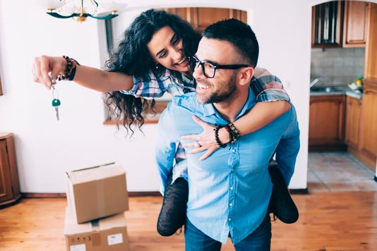 Young Couple Holding Keys Of New Apartment