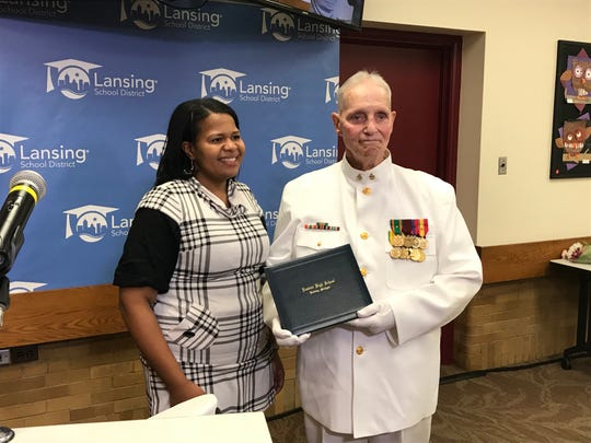 Lansing Board of Education President Rachel Lewis awarded Vietnam veteran Dann Huisken his high school diploma Thursday, Oct. 18, 2018. Huisken left high school before his graduation to enlist in the U.S. Navy.