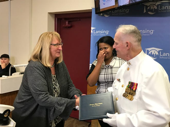 Vietnam veteran Dann Huisken shakes Lansing Superintendent Yvonne Caamal Canul's hand after receiving his high school diploma Thursday, Oct. 18, 2018, 48 years after he left high school to enlist in the U.S. Navy.