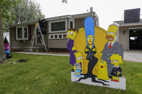 A hand-painted cutout of the Simpsons stands outside Manitowoc police Lt. Jeremy Kronforst's house as he hangs lights for the display in Manitowoc. Kronforst makes many of the displays himself.
