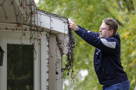 Manitowoc Police Department Lt. Jeremy Kronforst hangs lights on his house for his Frosty's Festival of Lights Halloween display in Manitowoc. Donations from the display go to benefit the Shop With a Cop program.