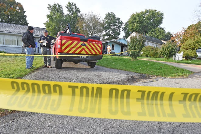 Investigators from the Mansfield Police and Fire departments examine the scene of a fire at 388 Opal Drive that resulted in a fatality and the loss of two pets.