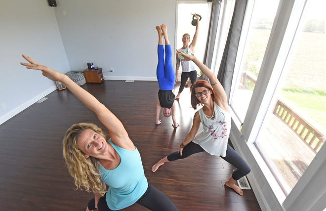 Yoga instructors Alissa Muntain, Karina Gledhill, Erika Hopkins and Amy Evans, from left, demonstrate yoga positions in their new yoga studio, Yoga 419, on Oct. 16. The new studio at 2680 Lexington Ave. opened in mid-September.