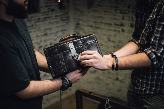 """Participants in an escape room at Breakout Games try to unlock a case as part of their effort to """"escape"""" the room. Escape rooms have become a popular form of entertainment for those seeking a different twist on Halloween."""