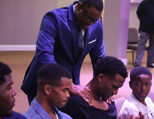 Memphis senior Jeremiah Martin prays at Divine Life Church.
