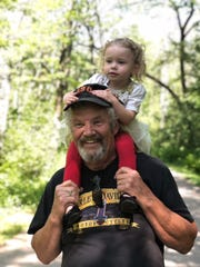 Mike Hoffer, great-grandfather of Raegan Dahm smiles as she rests on his shoulders. Hoffer died unexpectedly on Oct. 17.