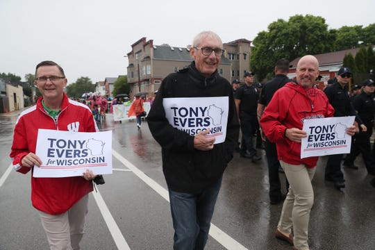 Tony Evers braves the rain to take part in the Milwaukee Pride Parade in June.