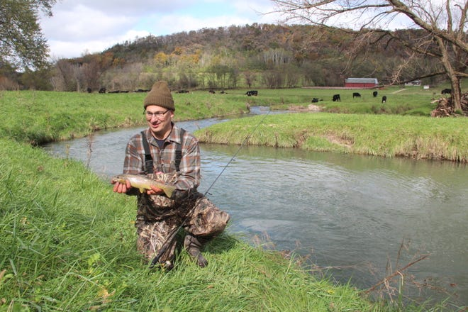 John Motoviloff holds a brown trout caught on Tainter Creek in Crawford County. This section of the stream, which features gently sloping banks as it passes through a farm with cattle, was undamaged by floods.